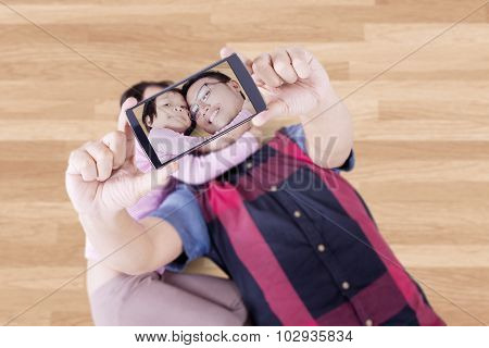 Father And His Child Taking Photo On The Floor