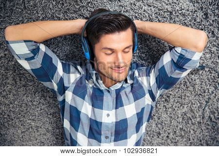 Portrait of a happy man relaxing on the floor with headphones at home