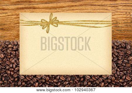 Postcard With Golden Bow On Roasted Coffee Beans And Wooden Background