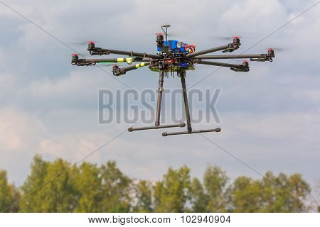 Multicopter in flight on trees background copter flying poster