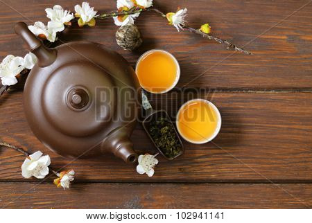 tea set (teapot, cups and different green tea) a wooden background, top view