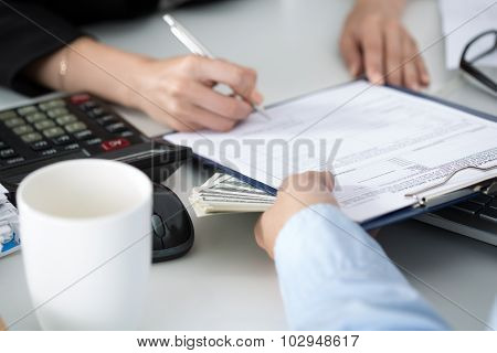 Woman Signing Documents For A Batch Of Hundred Dollar Bills