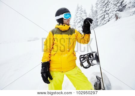 Close up portrait of male snowboarder wearing helmet with glasses, yellow jacket and pants, black gloves standing with snowboard in one hand  against blizzard - extreme sports concept