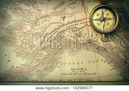 Antique brass compass over old XIX century map