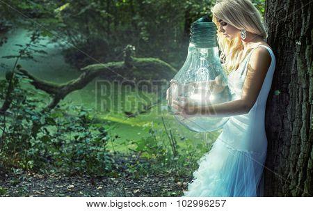 Art photo - stunning blonde beauty holding a big lightbulb