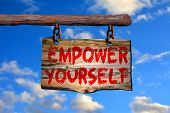 Empower yourself sign on old wood with a blurred sky on background poster