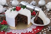 Christmas cake and slice with holly, bauble decorations and winter greenery over oak background. poster