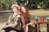 Pair of smiling women at outdoor pagan altar poster