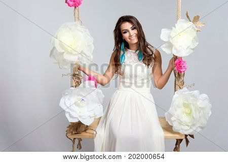 Smiling bride on seesaw in studio. Young brunette woman in wedding dress on seesaw.