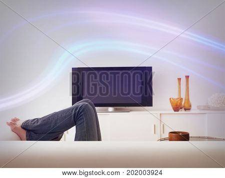 Low section of woman lying on sofa with television in contemporary living room