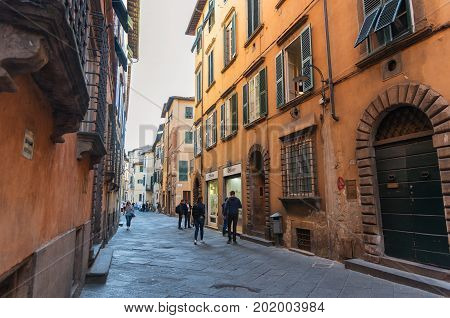 LUCCA, ITALY - MAY 23, 2017: Narrow old cozy street in Lucca, Italy. Lucca is a city and comune in Tuscany. It is the capital of the Province of Lucca