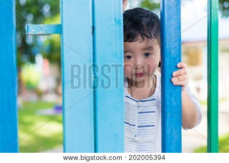 Sad Asian Kid Behind The Grid Trying To Escape. Shallow Dof