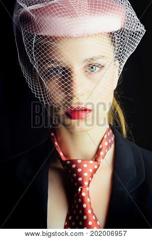 Lady posing on black background. Retro or vintage style concept. Fashion and accessories. Woman wearing pink hat with veil. Girl in tie with red dots on neck.