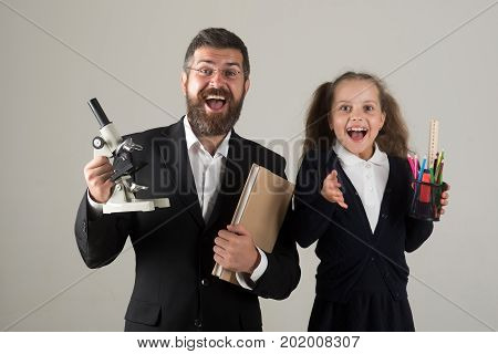 Father And Schoolgirl With Optimistic Faces On Grey Background