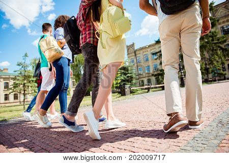 Cropped Close Up Low Angle Photo Shot Of Six Student`s Legs, Walking On The Paving Stones. Sunny Day