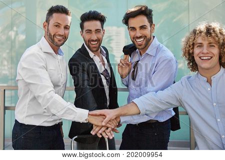 Happy Businessmen Holding Hands Together In Unity Gesture