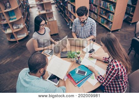 International Group Of Four Focused Clever Young Students Bookworms Studying In The College Library,