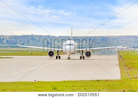 airplane on runway before takeoff - runway and green meadow in front