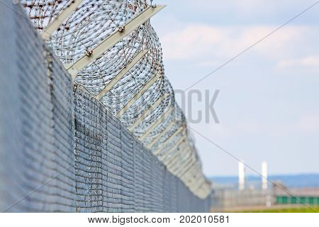 fence with barbed wire against blue sky with clouds