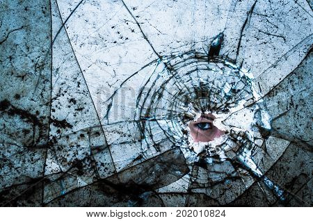 woman eye looking through break dirt window glass