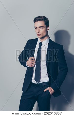 Vertical Portrait Of Confident Young Guy In Black Suit Touching Jacket And Holding Hand In Pocket
