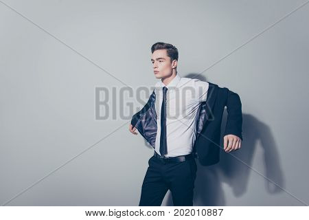 Young Handsome Guy With Perfect Hairstyle In Suit Wearing His Jacket Against Gray Background