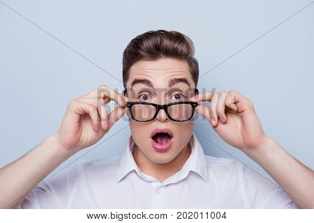 Close Up Portrait Of Wondered And Shocked Young Handsome Guy In White Shirt Touching His Glasses Wit