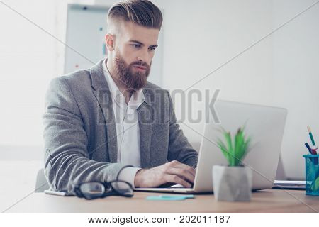 Handsome Concentrated Stylish Bearded Man In Jacket Using His Laptop For Sending Emails To Business