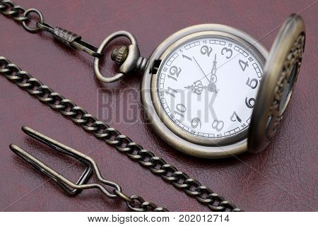old pocket watch in red leather background