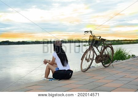 Asian Traveler Woman Sitting On Cement Ground Near The River With Bicycle In The Morning