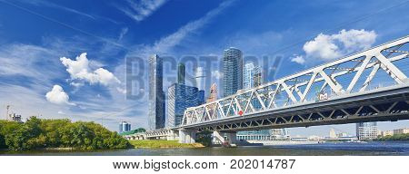 Moscow City panorama business center skyscrapers office buildings, luxury apartments and metal railway bridge with red train. Moscow city skyscrapers panorama. Modern european russian architecture