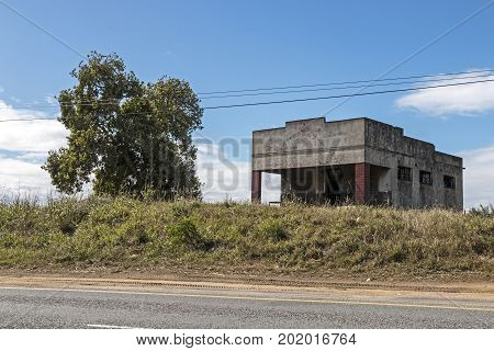 Old abandoned rural roadside store tree and powerlines against blue cloudy sky in South Africa