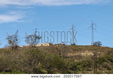 Rural Overhead Power Line Grid Against  Blue Cloudy Sky