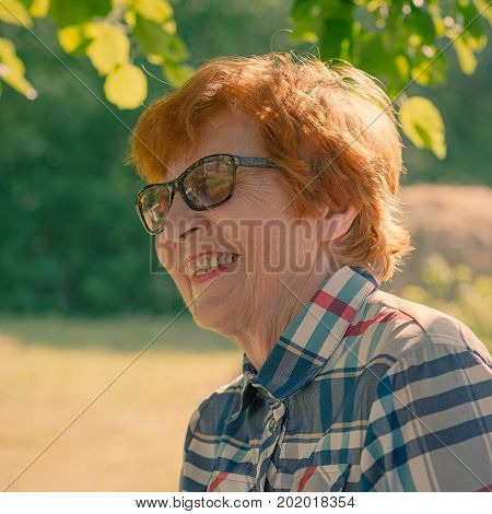Portrait of an emotional smiling woman with glasses. Age eighty years.