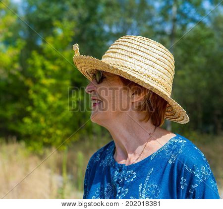 Portrait of a smiling woman in a straw hat and sunglasses. Age eighty years.