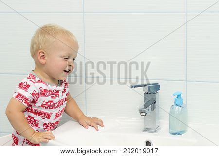 Close-up Portrait Of Cute White Caucasian Boy Toddler One Year Old Washing Hands In Bathroom And Loo