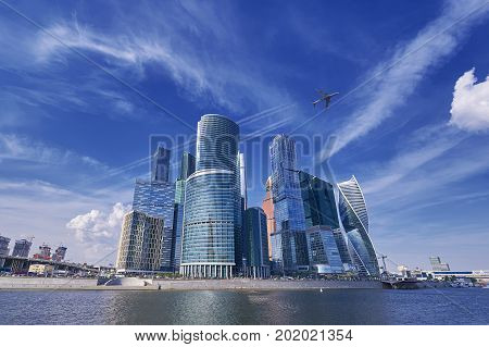 Vertical view on Moscow biggest business center Moscow City skyscrapers towers across river Moscow and flying passenger jet plane aircraft with trails among skyscrapers office buildings. Plane in sky among skyscrapers