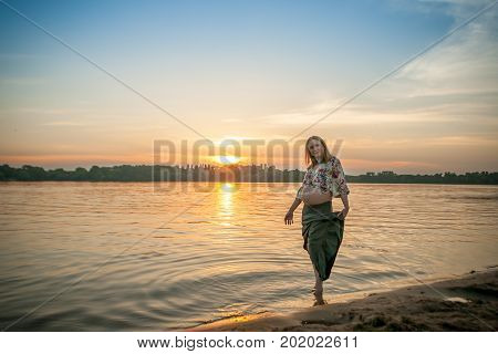 A pregnant beautiful woman on the river bank beach smiling with her mehandi ornament belly with love and care. Happy woman on sunset