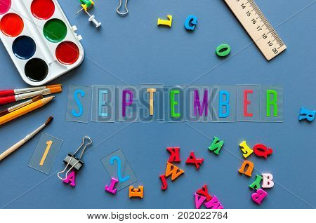 September 1st month of Autumn. Back to school concept. Teacher or student workplace background with school supplies on blue table.