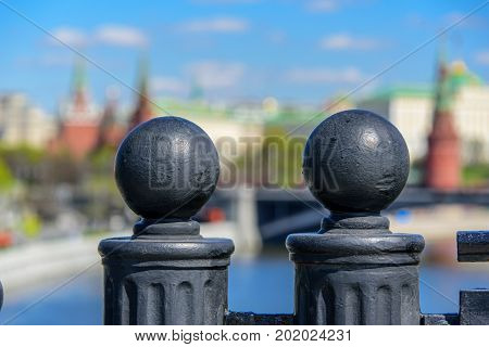 Two decorative fence spearheads on the background of blury Kremlin and Moscow river in the historical centre of Moscow city