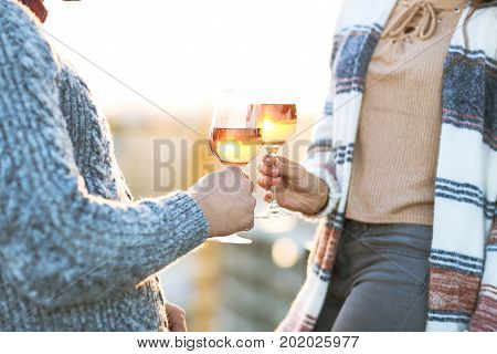 Man and woman with glass of rose wine on summer beach picnic