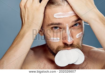Young guy with a beard on a gray background, cosmetic cream, cotton pads.