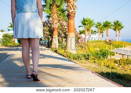 Travel And Vacation Concept - Back View Of Young Woman Walking On Summer Beach