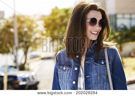 Young brunette woman in jacket and shades smiling