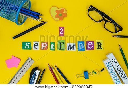 September 2nd. Day 2 of month, Back to school concept. Calendar on teacher or student workplace background with school supplies on yellow table. Autumn time.