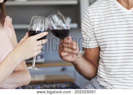 Couple toasting with red wine in kitchen close up