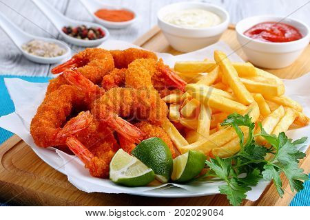 delicious crispy crunchy parmesan bread crumbs coating Fried Shrimps with lime wedges french fries and parsley on white plate on cutting board with spices and sauces view from above close-up
