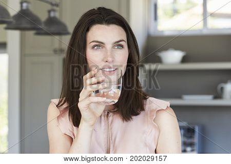 Young Beautiful brunette drinking water in kitchen