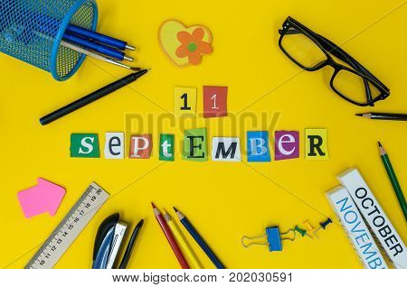 September 11th. Day 11 of month, Back to school concept. Calendar on teacher or student workplace background with school supplies on yellow table. Autumn time.