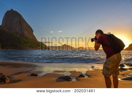 RIO DE JANEIRO, BRAZIL - NOVEMBER 31, 2016: Outdoor travel photographer at work, taking pictures of the Sugarloaf mountain at the sunrise on the shore of the Atlantic Ocean